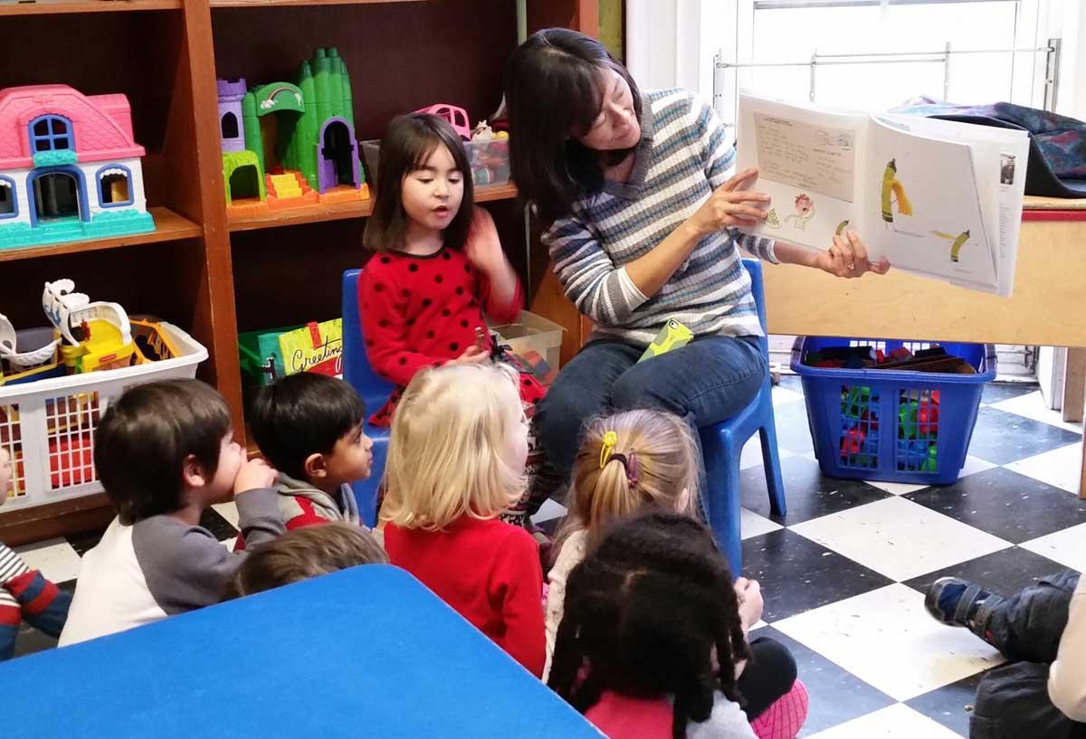 Teachers reads book to classroom