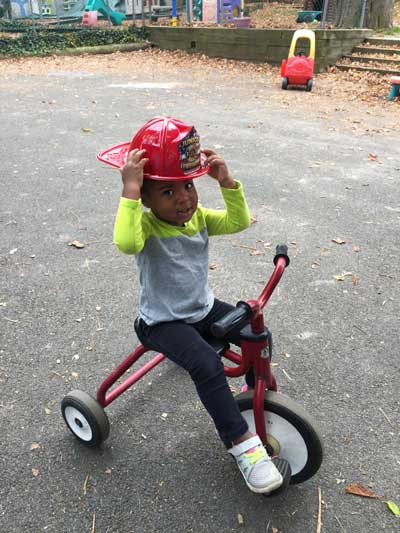 Boy riding tricycle with fireman hat
