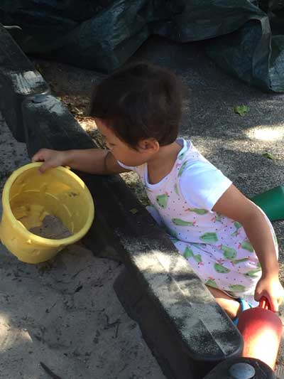 Girl with pail in sandbox